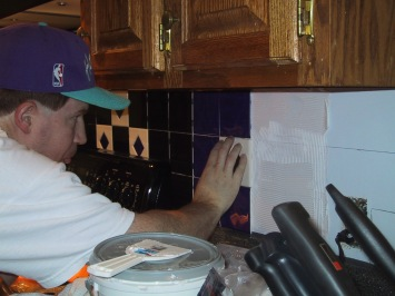 Greg tiling the kitchen backsplash at our old house in 2003